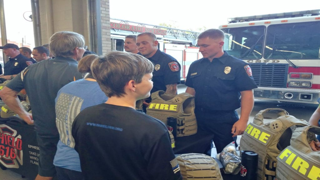 Firefighters at Colorado Springs Fire Station 1 talk with community members that helped donated ballistic gear through Shield 616.