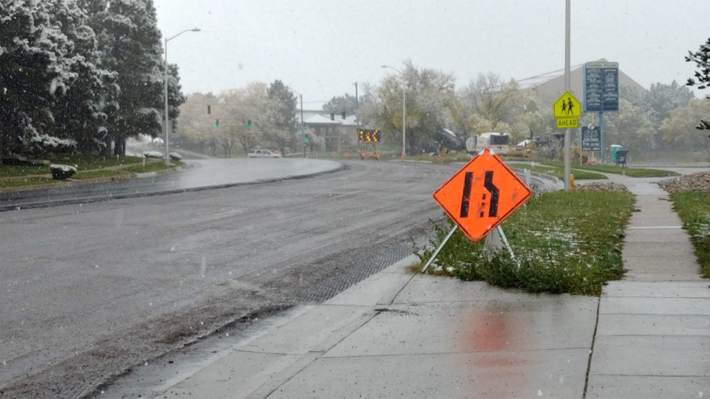 Snow falls in Colorado Springs on October 10, 2018, postponing a paving project at the intersection of North Carefree Circle and Oro Blanco Drive.