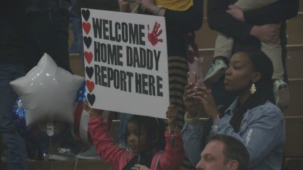 A mother and her daughter cheer as some 50 soldiers return to Fort Carson from a nine-month deployment in Afghanistan.