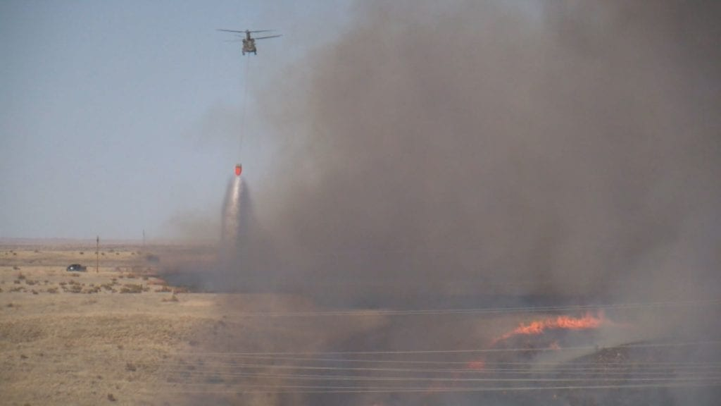 A helicopter drops water on the Carson Midway Fire on March 16, 2018.